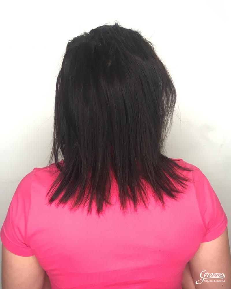 девушка в розовой футболке с темными волосами стоит спиной